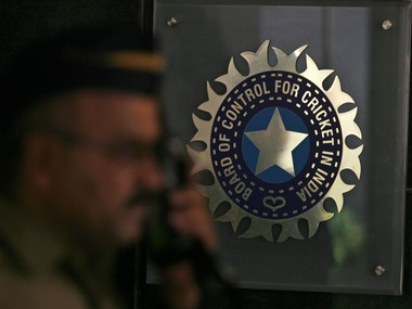 A policeman walks past logo of BCCI in Mumbai. Reuters