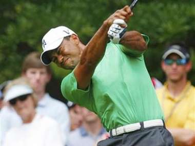 Woods grimaces as he hits his tee shot on the eighth hole during the second round of the Wells Fargo Championship PGA golf tournament in Charlotte. Reuters