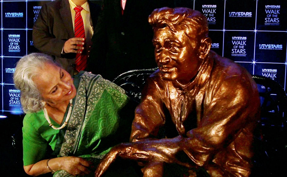 Veteran actress Waheeda Rehman takes a closer look of a life-size statue of legendary actor Dev Anand after its unveiling to mark his first death anniversary in Mumbai on Tuesday. PTI