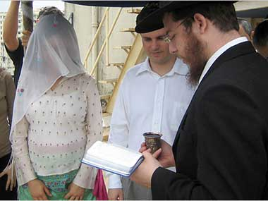 In this picture Rabbi Gavriel Holtzberg, right performed a Jewish wedding in Mumbai in India in 2006 as his wife Rivka Holtzberg, left looked on. Reports indicate the couple may have been brutally tortured before being killed by the terrorists.