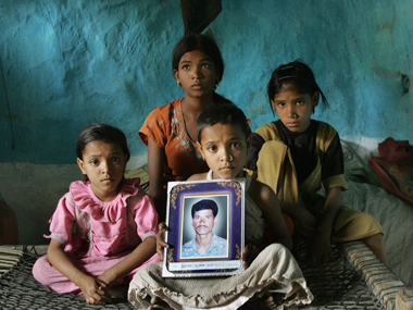 Four daughtersof the late 35-year-old Indian cotton farmer Neelkhant Haste mourn his death with a picture of him, after Haste committed suicide by consuming pesticide. Desperate and debt-ridden with loan sharks demanding up to 120 percent annual interest, the failed harvests and tumbling prices have driven businesses to the wall and farmers to suicide. AFP
