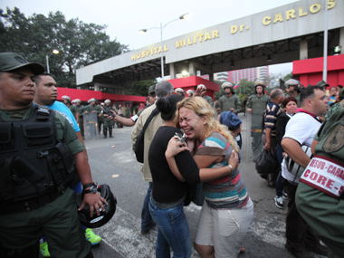 People also gathered outside the military hospital where Chavez died. AP