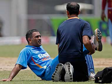 Mahendra Singh Dhoni, left, is tended by the team physiotherapist after injuring his leg during the Tri-Nation Series cricket match against the West Indies in Kingston, Jamaica. AP