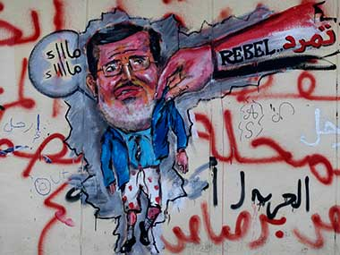 "Graffiti depicting Egypt's Islamist President Mohammed Morsi with an Arabic writing that reads: ""Leave, right"" covers an outer wall of the presidential palace in Cairo, Egypt. AP"