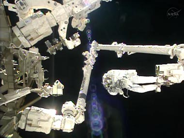 In this image made from video provided by NASA, Italian astronaut Luca Parmitano stands on the end of a robotic arm during a spacewalk outside the International Space Station. AP