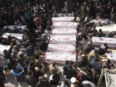Shi'ite Muslims sit beside the covered bodies of victims who were killed in Tuesday night's bomb attack. Reuters