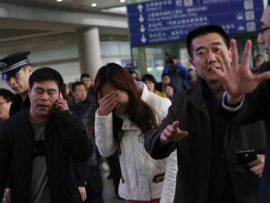 A woman (C), believed to be the relative of a passenger onboard Malaysia Airlines flight MH370, covers her face as she cries at the Beijing Capital International Airport in Beijing. Reuters