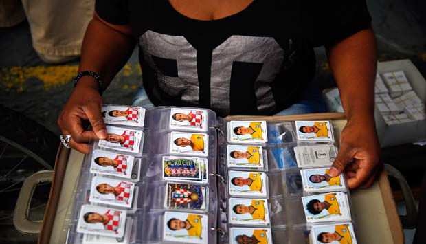 A woman sorts her Panini soccer World Cup stickers collection while sitting at a trading and meeting point for sticker collectors in downtown Sao Paulo: Reuters