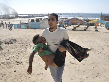 A Palestinian man carries the body of a boy killed by Israeli shells on a beach in Gaza City. Reuters image