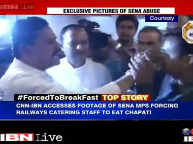 The MPs are seen force-feeding the Muslim staffer. Screenshot from Ibnlive