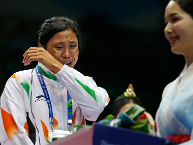 Sarita Devi cries looking at a medal after she refused to accept her bronze medal during the medal ceremony. AP