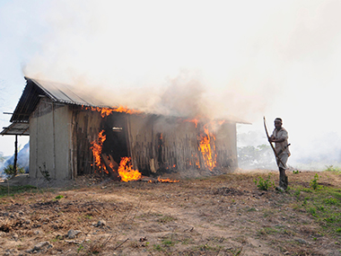 A villager stands by a burning house which belonged to the Bodo tribesmen. Retaliatory attacks flared up in a few Assam villages on Ffriday. Reuters