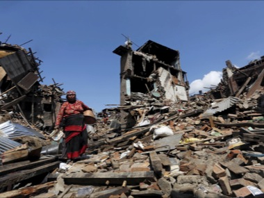 A woman carrying belongings walks past collapsed houses after devastating earthquake. Reuters