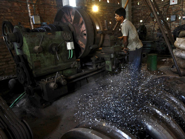 A worker makes gear parts for cranes inside a workshop on the outskirts of Kolkata