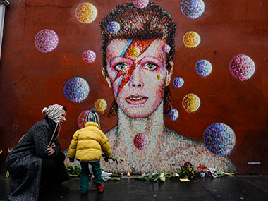 A man takes a photograph on his smartphone of floral tributes left beneath a mural of British singer David Bowie. AFP