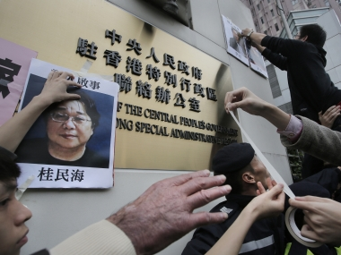 Protesters try to stick photos of missing booksellers during a protest outside the Liaison of the Central People's Government in Hong Kong. AP