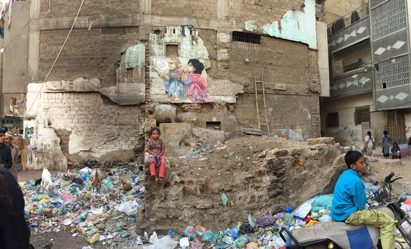 A child sits in front of the completed painting in Karachi's Lyari. Image courtesy: Shilo Shiv Suleman