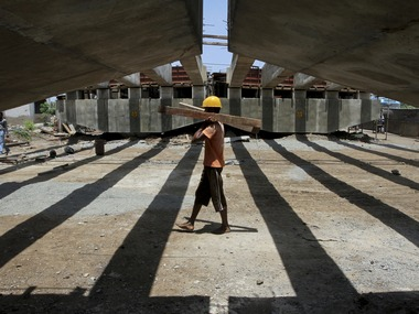 A worker carries pieces of wood at the construction site of a flyover bridge in the southern Indian city of Chennai July 18, 2011. Indian GDP is expected grow 7.8 percent in the June-quarter and then slow to 7.5 percent in the next quarter, but pick up after that to stay above 8 percent until at least the end of 2012, according to a Reuters quarterly poll. REUTERS/Babu (INDIA - Tags: EMPLOYMENT BUSINESS CONSTRUCTION)
