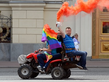 Gay and LGBT rights activist Nikolai Alexeyev holds a flare as he rides a quad-bike during an unauthorized gay rights activists rally in central Moscow in a file photo. AFP