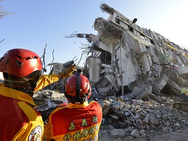 Two rescue workers stand next to the remains of the Wei-Kuan complex which collapsed in the 6.4 magnitude earthquake in Tainan. AFP
