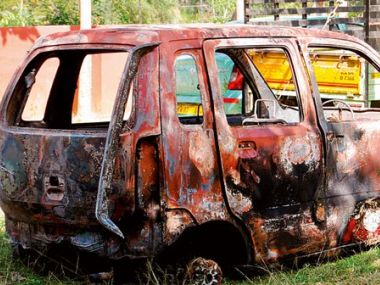 The charred remains of the car burnt by mob in Bengaluru. Image courtesy: Twitter