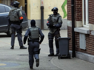 A special operations officer runs during a police raid in the Molenbeek neighbourhood of Brussels, Belgium on Friday. AP