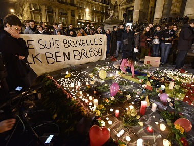 "People holding a banner reading ""I am Brussels"" behind flowers and candles to mourn for the victims at Place de la Bourse in the centre of Brussels on Tuesday. AP"