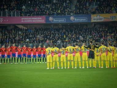 Spain's and Romania's national team members observe a minute of silence in the memory of Johan Cruyff. AFP