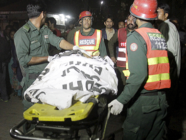 Rescue workers move a body from the site of a blast outside a public park in Lahore on Sunday. Reuters