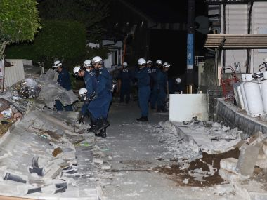 Police officers search for victims under collapsed stone walls in the town of Mashiki. AFP