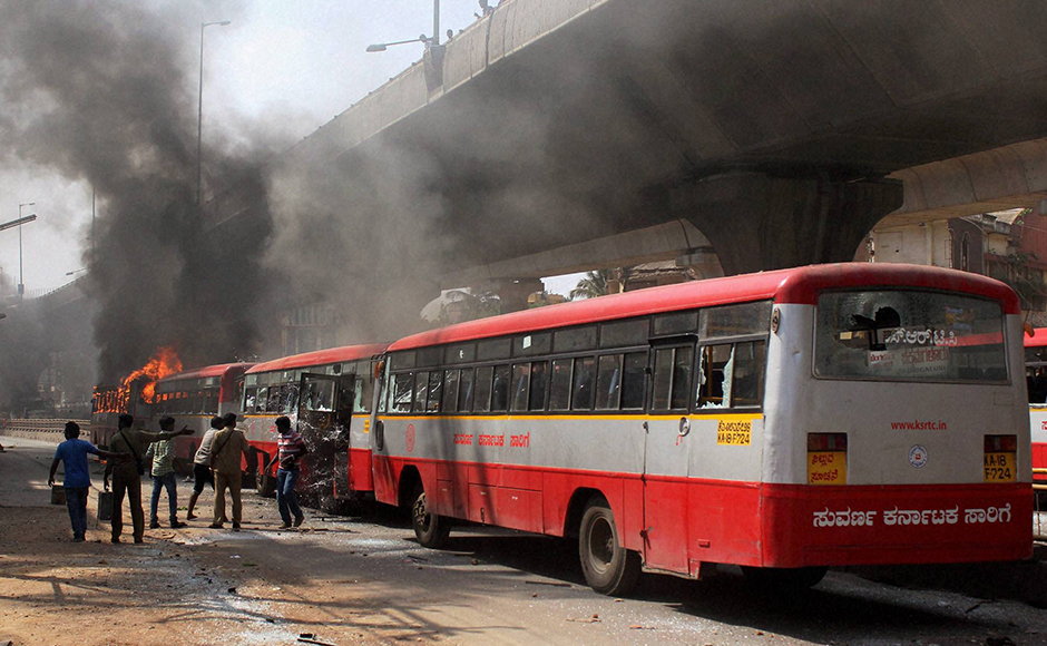 Charred buses which were torched by garment workers during a protest rally over EPF withdrawal norm, in Bengaluru on Tuesday. PTI