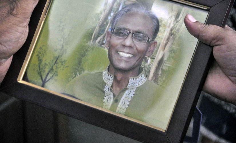 A man holds a portrait of Bangladeshi professor Rezaul Karim Siddique. AFP