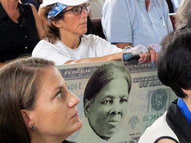 File image of a woman holding a sign supporting Harriet Tubman for the $20 bill. AP