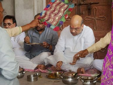 BJP President Amit Shah having a meal with a dalit family in Varanasi on Tuesday. PTI