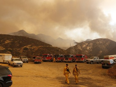 Fire trucks and horse trailers stage outside Wildlife Waystation in Santa Clarita, Calif., on Saturday, July 23, 2016. A wildfire burning in the mountainous Angeles National Forest north of Los Angeles has grown to more than 17 square miles. The Wildlife Waystation has about 400 animals on 160 acres within the national forest. (Katharine Lotze/The Santa Clarita Valley Signal via AP)