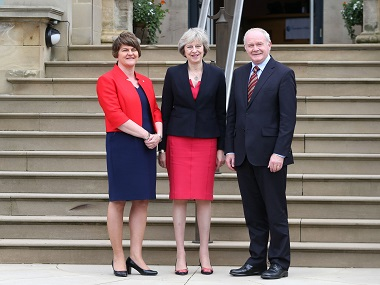 Britain's Prime Minister Theresa May, (centre), is greeted by Northern Ireland's First Minister Arlene Foster (left) and Deputy First Minister Martin McGuinness upon arrival at Stormont Castle in Belfast, Northern Ireland. PA via AP