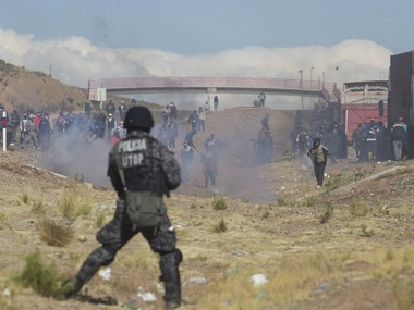 """Independent miners clash with the police as they run from clouds of tear gas during protests in Panduro, Bolivia, Thursday, Aug. 25, 2016. Government officials said that the striking miners kidnapped and beat to death the country's deputy interior minister after he traveled to the area to mediate in the bitter conflict over mining laws. Government Minister Carlos Romero called it a """"cowardly and brutal killing"""" and asked that the miners turn over the body of his deputy, Rodolfo Illanes. AP"""