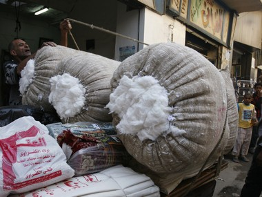 An Egyptian tradesman prepares to move a sack full of cotton to a car for sale at a market in Cairo June 24, 2008.     Reuters
