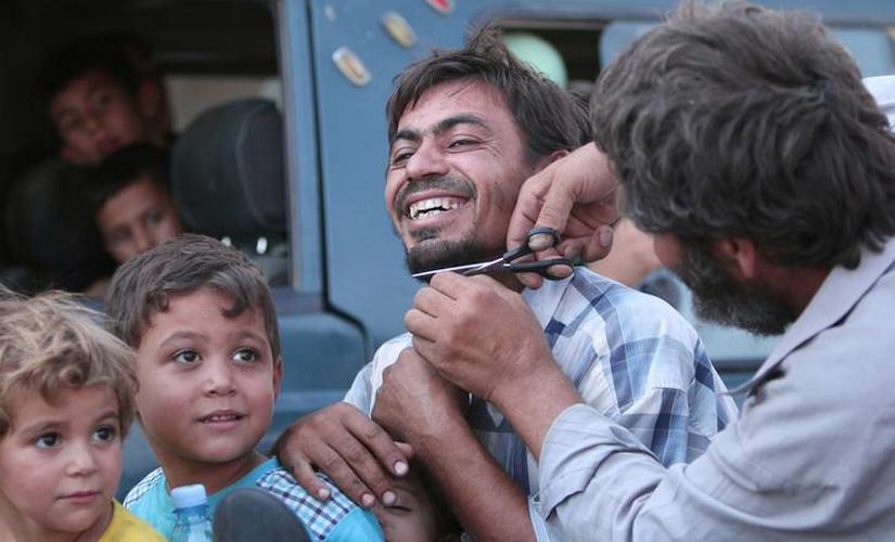A man cuts the beard of a civilian who was evacuated with others by the Syria Democratic Forces from an IS-controlled neighbourhood in Aleppo Governorate, Syria. Reuters
