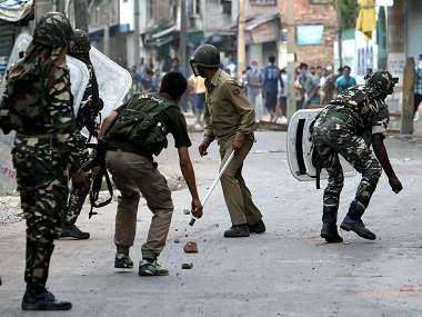 Security jawans chashing away stone throwing youths during a clash in Srinagar on Thursday. PTI