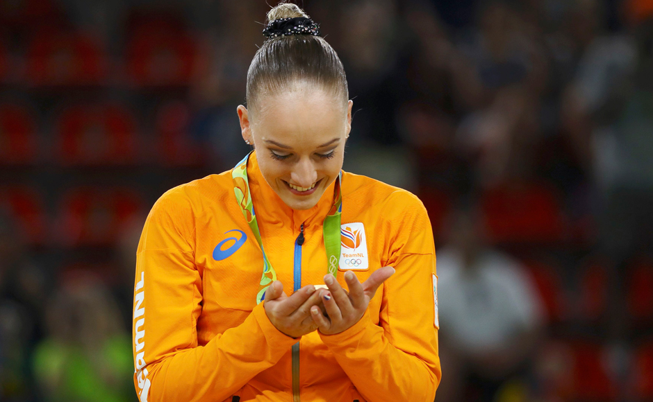 Sanne Wevers of Netherlands looks at her gold medal on the podium after winning Women's Balance Beam finals. Reuters