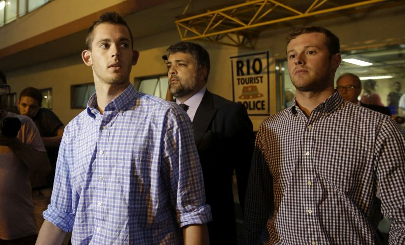 American Olympic swimmers Gunnar Bentz and Jack Conger leave a police station. AP