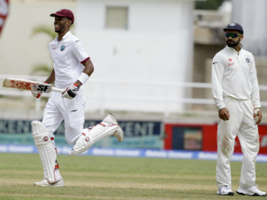 Virat Kohli (right) looks on as Roston Chase completes his maiden Test century. AP