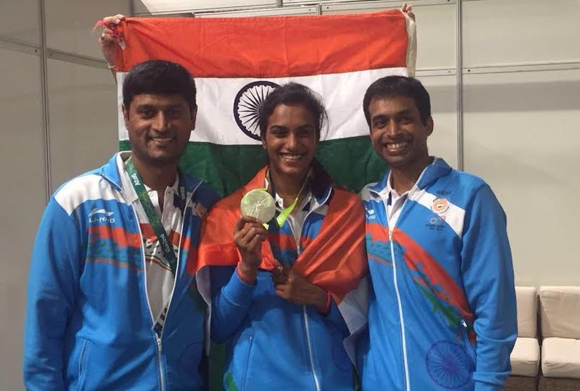 with PV Sindhu and Gopichand pose with her silver medal. Image Credit:
