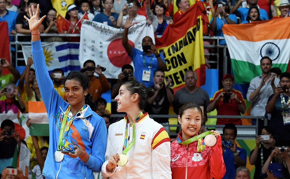 Silver medalist PV Sindhu of India, gold medalist Carolina Marin of Spain and bronze medalist Nozomi Okuhara of Japan celebrate during the medal ceremony after the Women's Singles Badminton competition on Day 14 of the Rio 2016 Olympic Games. PTI