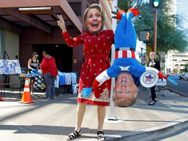 A man wears a mask depicting Democratic U.S. presidential candidate Hillary Clinton while holding a doll depicting Republican presidential nominee Donald Trump in Phoenix. Reuters
