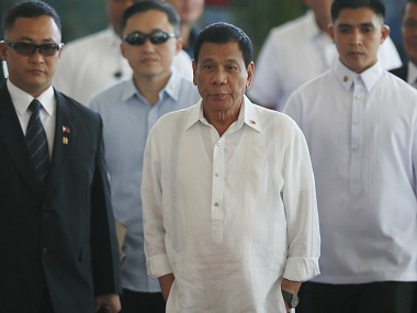 """Philippine President Rodrigo Duterte, center, is escorted to the podium for a news conference prior to boarding his flight for a three-day official visit to Japan at the Ninoy Aquino International Airport in suburban Pasay city, south of Manila, Philippines, Tuesday, Oct. 25, 2016. Duterte lashed out anew at the United States following Monday's interview with U.S. Assistant Secretary of State for East Asian and Pacific Affairs Daniel Russel who said that the Philippine president's controversial remarks and a """"real climate of uncertainty"""" about the government's intentions have sparked consternation in the U.S. and other governments and in the corporate world. (AP Photo/Bullit Marquez)"""