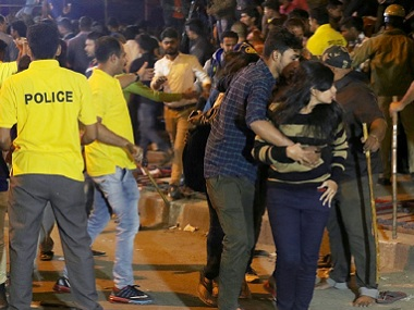 Police personnel try to manage crowds during a New Year's Eve brawl in Bangalore. AFP