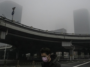A man wearing a face mask crosses what is usually a busy street in Beijing on Thursday. By Gilles Sabrié © 2020 The New York Times