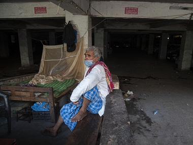 An Indian laborer wearing a mask sits near a wholesale vegetable market. AP